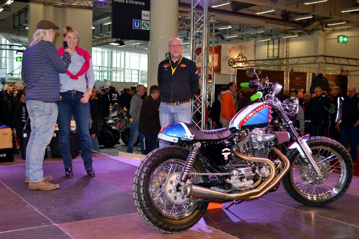 (Bildnachweis: Harley-Davidson Hamburg-Nord) Bild 1 zeigt Moderator Bernward Büker, Gewinnerin Kerstin C. und Volker Stan von Harley-Davidson Hamburg-Nord.
