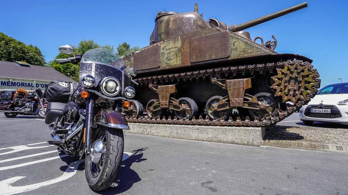 Das Foto zeigt die Harley-Davidson Heritage Classic vor einem Sherman-Panzer am Omaha Beach zum 75th Anniversary