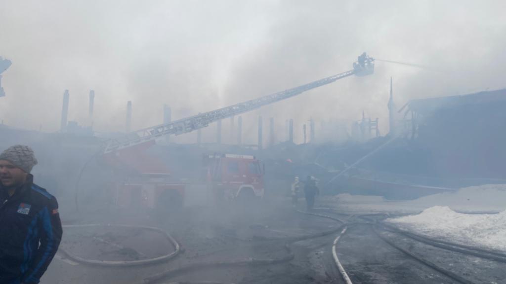 I vigili del fuoco operano con la scala girevole nel fumo denso