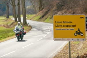 Ein Motorradfahrer fährt an einem Schild an der Landstrasse im Gelbachtal vorbei, das Biker für rücksichtsvolle Fahrweise sensibilisieren soll. Vor dem Saisonstart startet der ADAC Mittelrhein e.V. unterstützt vom Land Rheinland-Pfalz ein Pilotprojekt gegen Motorradlärm.
